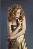 Beautiful red-haired girl in short dress hugging herself. Sexy red-haired girl in a short golden-fitting dress Royalty Free Stock Image