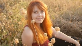 Beautiful red-haired girl sits on the ground in a field among dried flowers and enjoys nature at sunset, young woman relaxing, con. Cept of rest, healthcare stock video