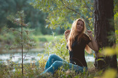 Beautiful red-haired girl sitting near river at forest and stretched Royalty Free Stock Image