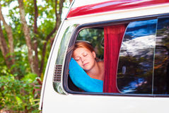 A beautiful red-haired girl is sleeping on the bus while traveling. Stock Images