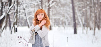 Beautiful red-haired girl in a snowy forest. Portrait of a young girl in sherstnyanoy jacket in winter forest Stock Photo