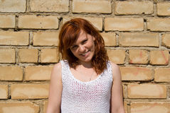 A beautiful red-haired girl standing by the wall Stock Photos