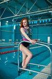 A beautiful red-haired girl stands on the steps of the swimming pool ladder. A woman is engaged in a healthy lifestyle. Water stock photos
