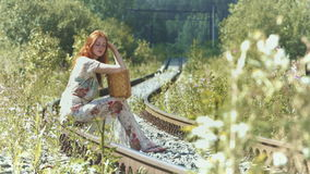 A girl with a suitcase is sitting on the rails. A beautiful red-haired girl with a suitcase on her lap sits on the railroad track and looks at the camera. Slow stock video footage