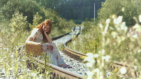 A girl with a suitcase is sitting on the rails. stock footage