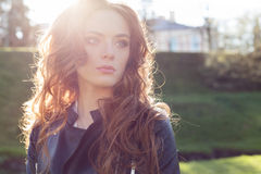 Beautiful red-haired girl in the sun in a black jacket in the town park stock image