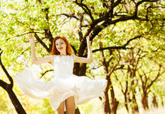 Beautiful red-haired girl in a white dress in the autumn air hap stock photos