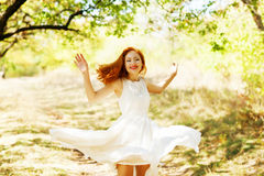 Beautiful red-haired girl in a white dress in the autumn air hap royalty free stock photo