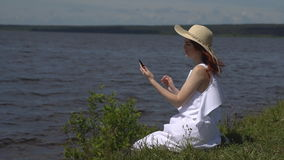 Beautiful red-haired girl in a white summer dress uses a cell phone sitting on the shore and rivers stock video
