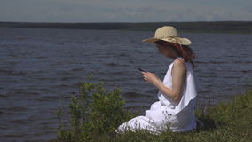 Beautiful red-haired girl in a white summer dress uses a cell phone sitting on the shore and rivers stock video footage