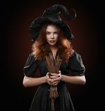 Beautiful red-haired girl in the witch costume Stock Images