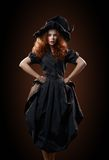 Beautiful red-haired girl in the witch costume Royalty Free Stock Image