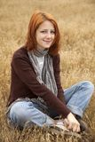 Beautiful red-haired girl at yellow autumn grass. Royalty Free Stock Photos