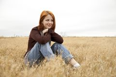 Beautiful red-haired girl at yellow autumn grass. Stock Photo