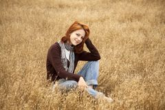 Beautiful red-haired girl at yellow autumn grass. Stock Photography