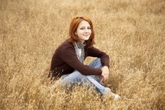 Beautiful red-haired girl at yellow autumn grass. Stock Photos