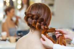 Beautiful red-haired hairy girl, hairdresser weaves a French braid, close-up in a beauty salon. Professional hair care and creating hairstyles royalty free stock photo