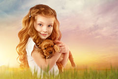 Beautiful red-haired little girl with red puppy outdoor. Kid Pet Friendship. Beautiful red-haired little girl with red puppy in field at sunset. Fashion, style Royalty Free Stock Images