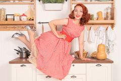 Beautiful red-haired pinup smiling happily girl posing in a retro red dress in the kitchen alone royalty free stock photos