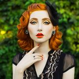 Beautiful red-haired retro girl with clean healthy skin and blue eyes. Fashion vintage model stock photo