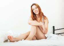Beautiful red-haired sensual girl in shirt awaking on white shee Stock Images
