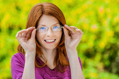Beautiful red-haired smiling young woman with glasses. Royalty Free Stock Image