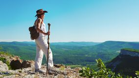 The girl traveler in a cowboy hat and white clothes stands on the top of the mountain and admires the stunning views of. A beautiful red-haired traveler girl in stock footage