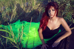 Beautiful red haired woman in black corset and long tail green veiling skirt leaning on the shabby upside down wooden boat. Portrait of young beautiful red stock image