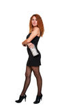 Beautiful red-haired woman in black dress and clut Stock Photo