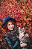 Beautiful red-haired woman in blue hat and leather jacket walking with cat in autumn red park. stock photography