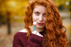 Beautiful red haired woman with candy in hand, intrigue stock photo