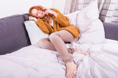 Beautiful red-haired woman curls herself comfortably on her couc Stock Photo