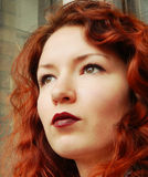 Beautiful red-haired woman with curly hair and burgundy lips Stock Photography