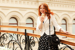 Beautiful red-haired woman. Is eating ice cream and walking in the mall Stock Photography