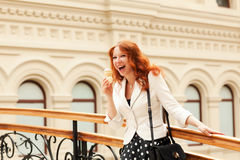 Beautiful red-haired woman. Is eating ice cream and walking in the mall Stock Image