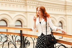 Beautiful red-haired woman. Is eating ice cream and walking in the mall Stock Photos