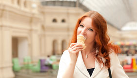 Beautiful red-haired woman. Is eating ice cream and walking in the mall Royalty Free Stock Photography
