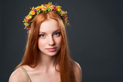 Beautiful red haired woman in flower wreath. Closeup of beautiful red haired woman in flower wreath Royalty Free Stock Image