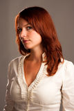 Beautiful red-haired woman on gray. Subtly lighted shot of a beautiful girl royalty free stock photography
