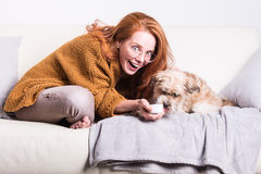 Beautiful, red-haired woman with her dog on the couch Stock Images