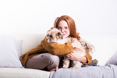 Beautiful, red-haired woman with her dog on the couch Stock Image