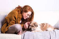 Beautiful, red-haired woman with her dog on the couch Stock Photography