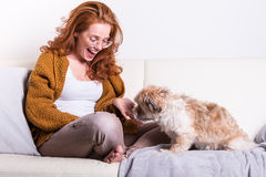 Beautiful, red-haired woman with her dog on the couch Royalty Free Stock Photography