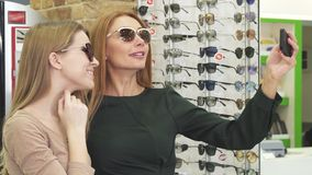 Gorgeous happy women taking selfies while shopping eyewear stock video footage