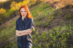 Beautiful red haired woman holding bouquet Royalty Free Stock Photos