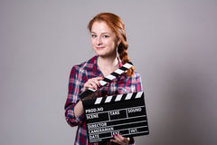 Beautiful red-haired woman holding a movie clapper, isolated ove Stock Photography