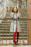 Beautiful red-haired woman. Holds hands behind bars Stock Photo