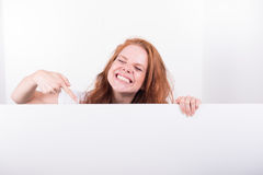 Beautiful red-haired woman holds a white board Royalty Free Stock Photo