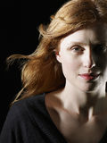Beautiful Red Haired Woman Looking At Camera. Closeup of beautiful red haired woman looking at camera on black background Stock Photo