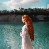 Beautiful red-haired woman in a luxurious renaissance dress on the background of a lake. With blue water stock photos